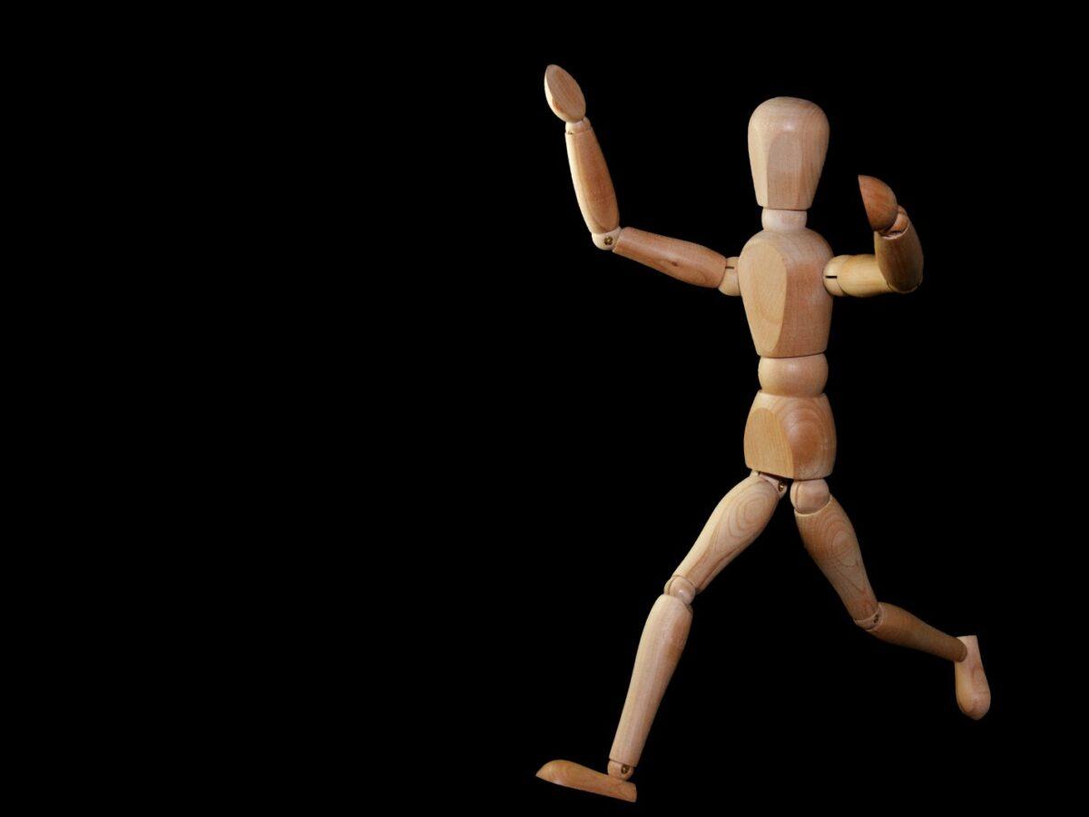Eine Holzfigur in Menschengestalt wird im Laufen dargestellt.