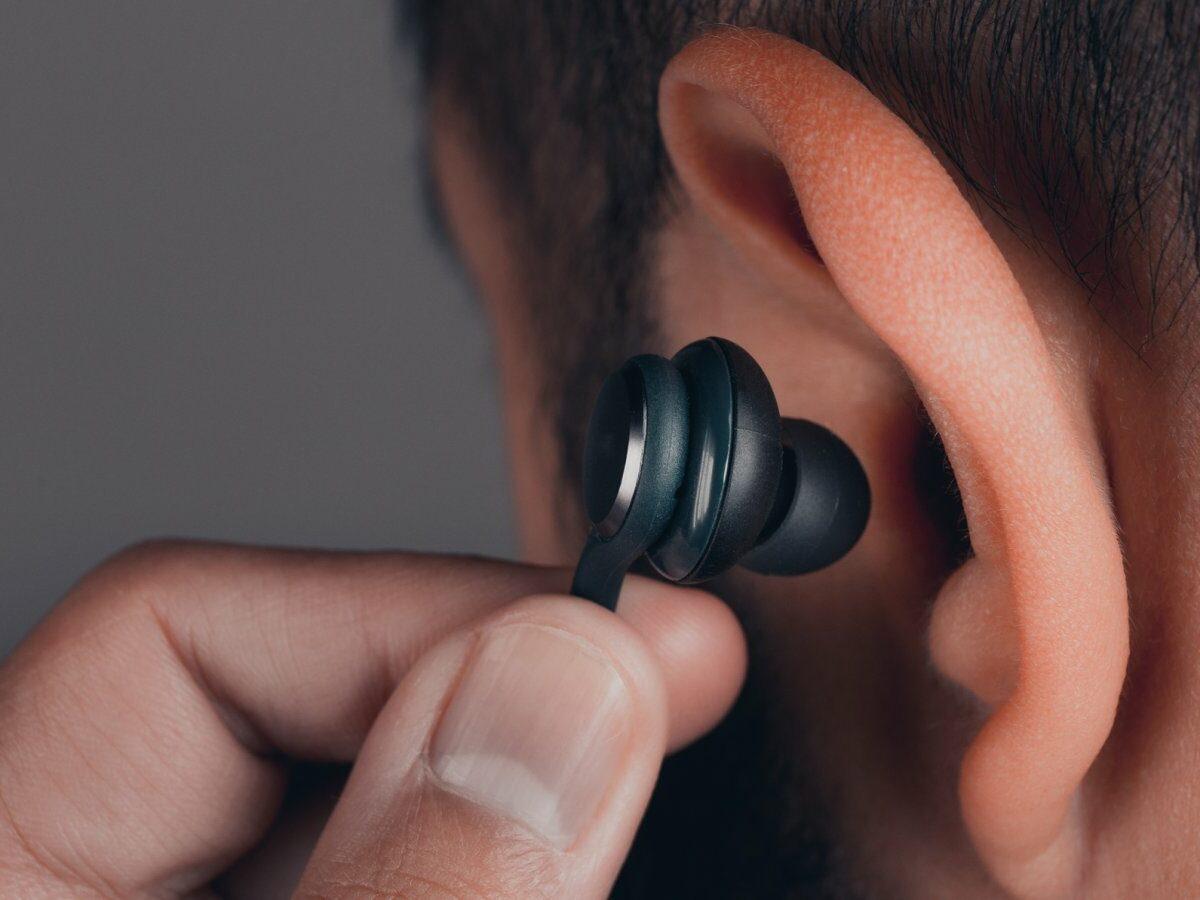 Man steckt sich In-Ear-Kopfhörer ins Ohr.