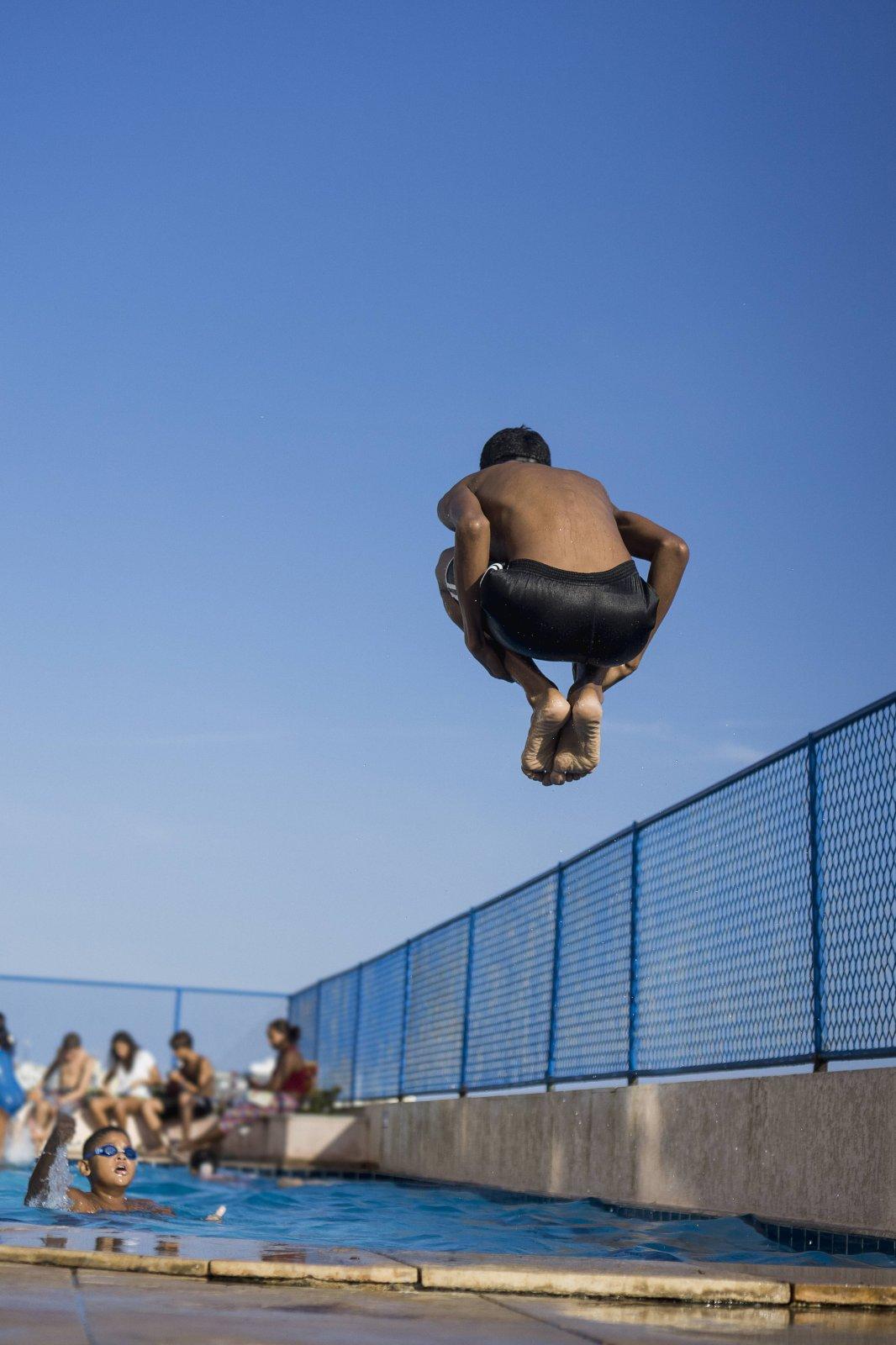 Ein Junge springt in den Swimming Pool