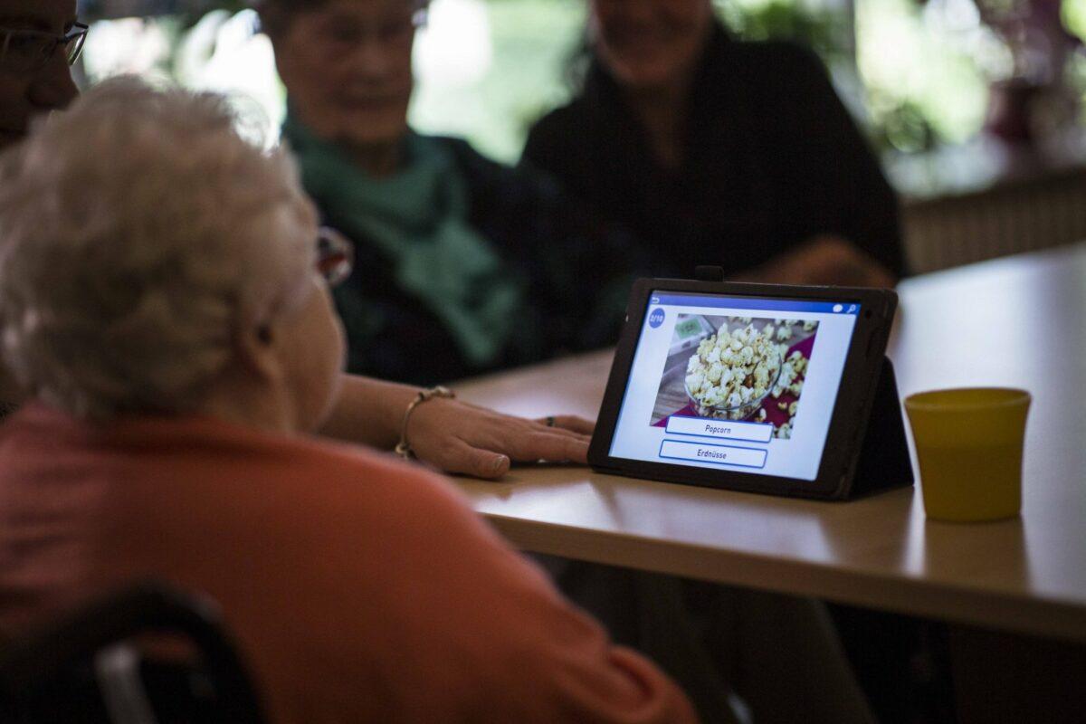 Eine ältere Dame schaut auf einen Tablet-PC.