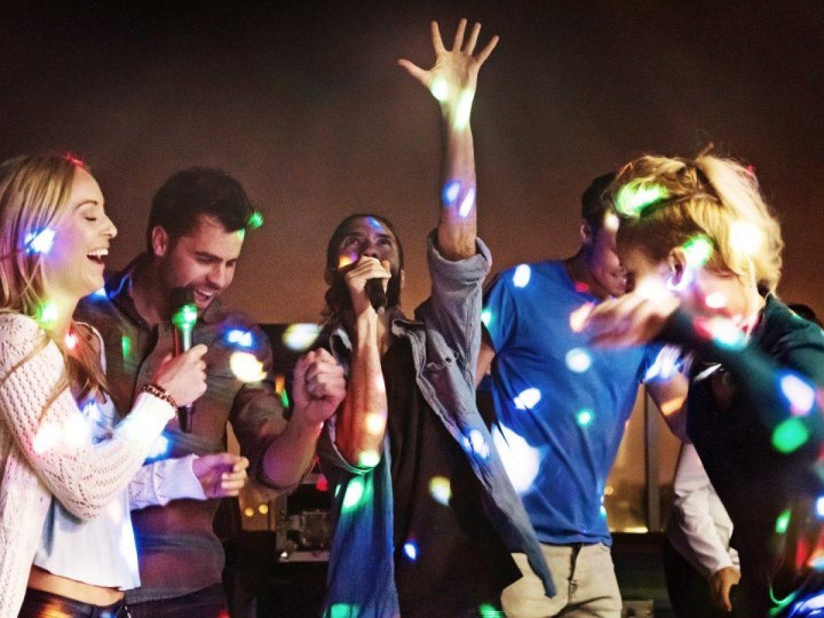 Mehrere Personen singen gemeinsam Karaoke.