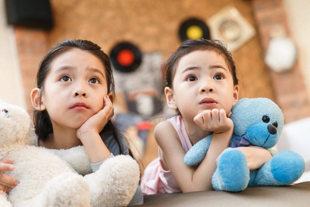 Zwei Kinder liegen auf dem Bett und gucken Fernsehen.