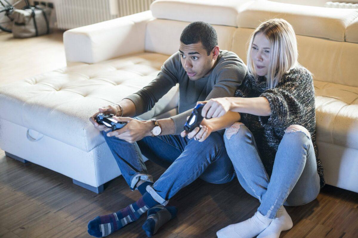 Ein Mann und eine Frau spielen auf einer Konsole.