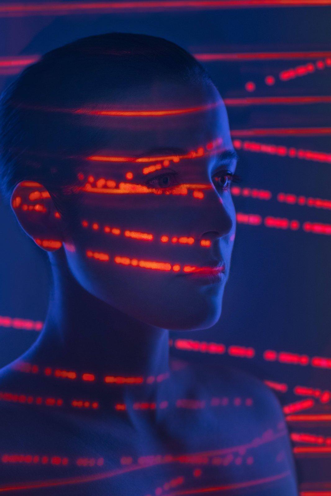 Das Bild zeigt ein Schattenbild einer Frau mit roten Lichtern auf dem Gesicht.