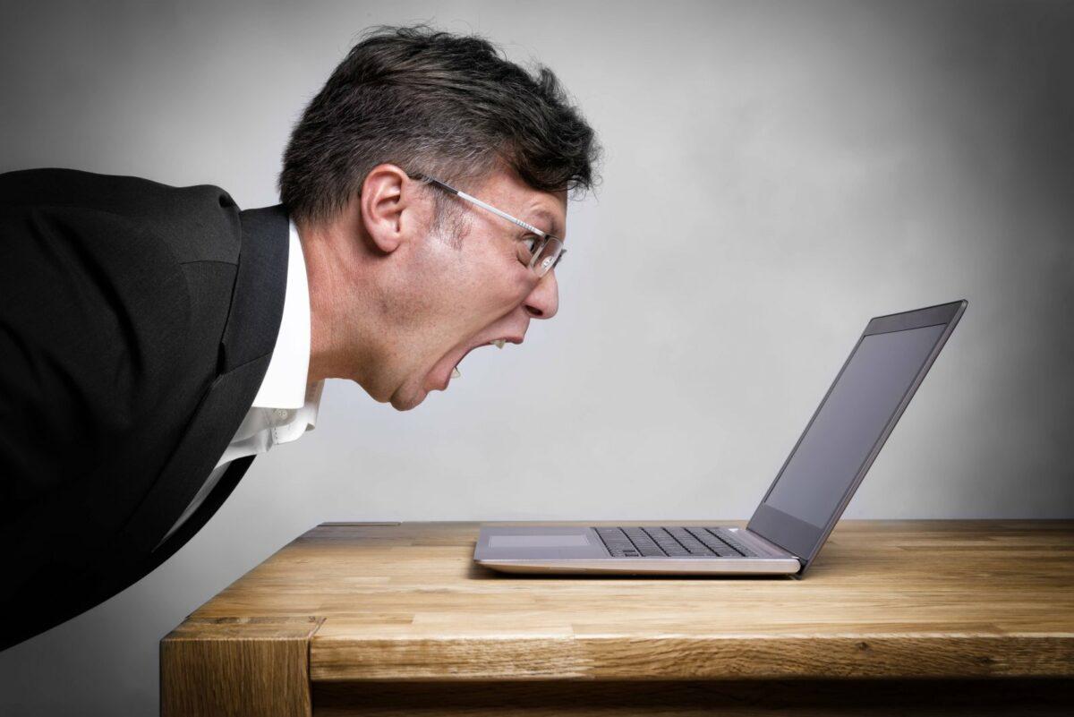 Mann schreit Laptop an.