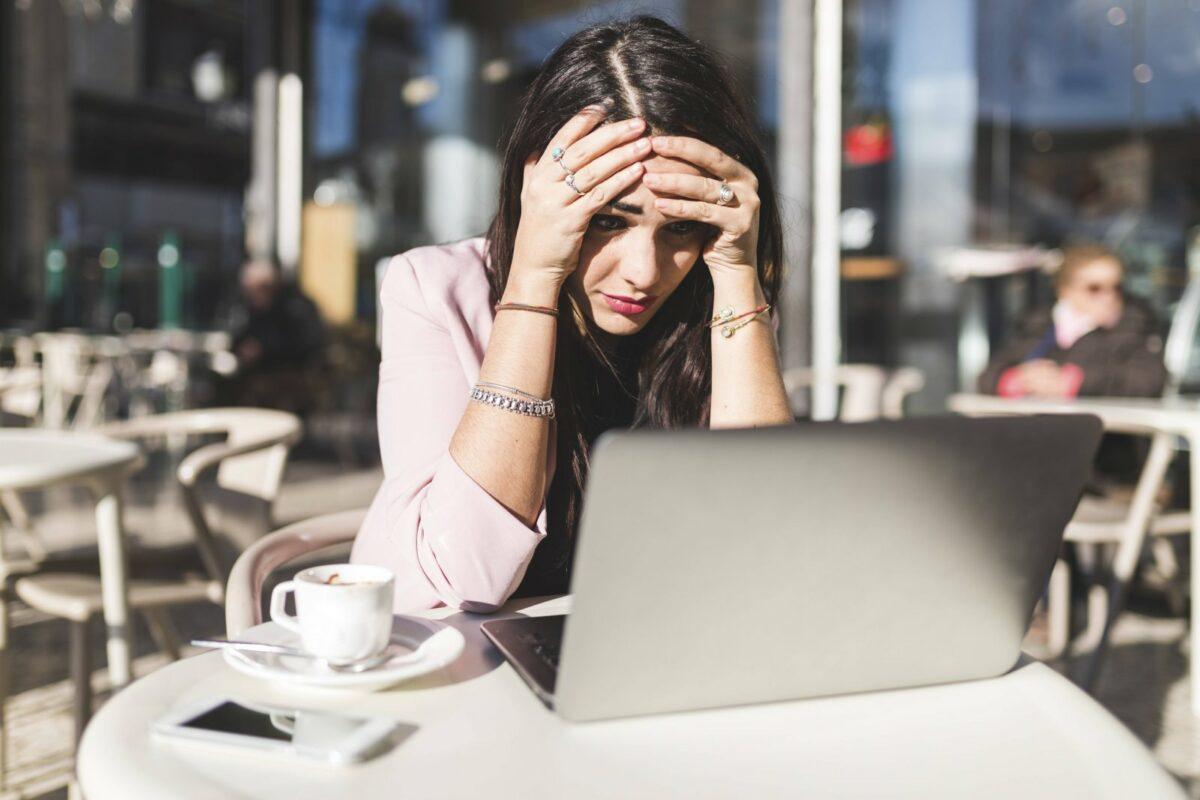 Eine Frau guckt auf ihren Laptop und ist verzweifelt