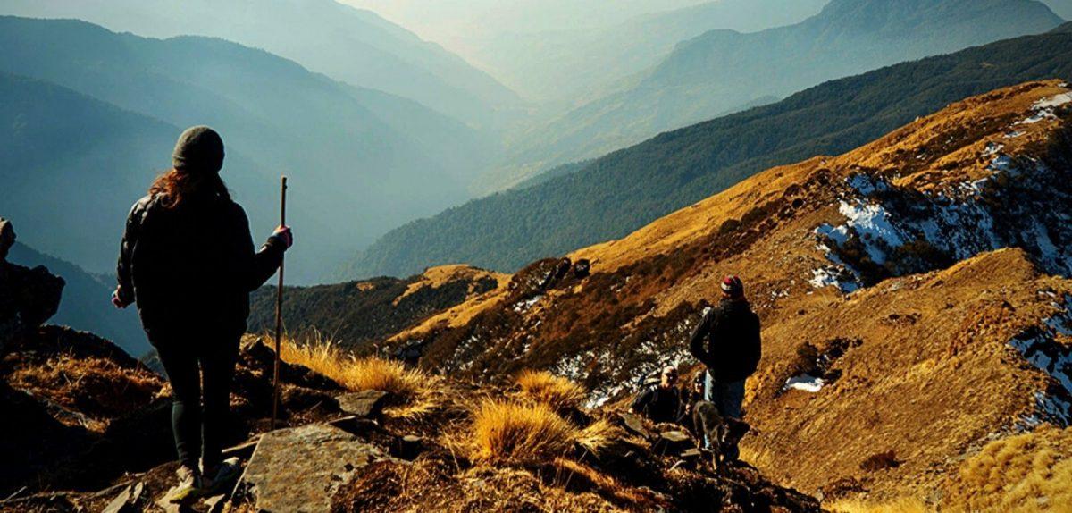 Wanderndes Pärchen blickt auf ein Bergpanorama.