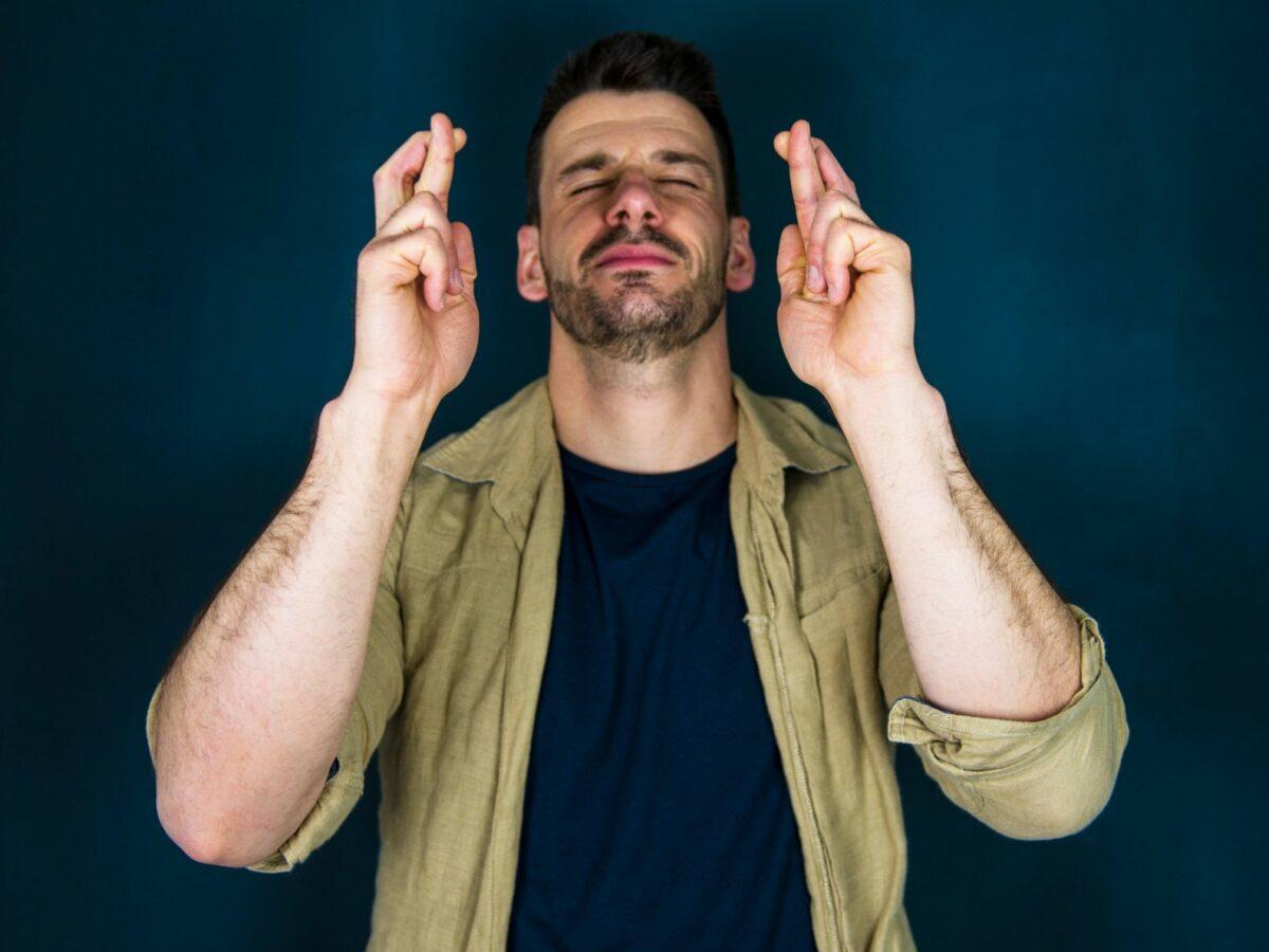 Mann überkreuzt seine Finger und schaut zum Himmel.