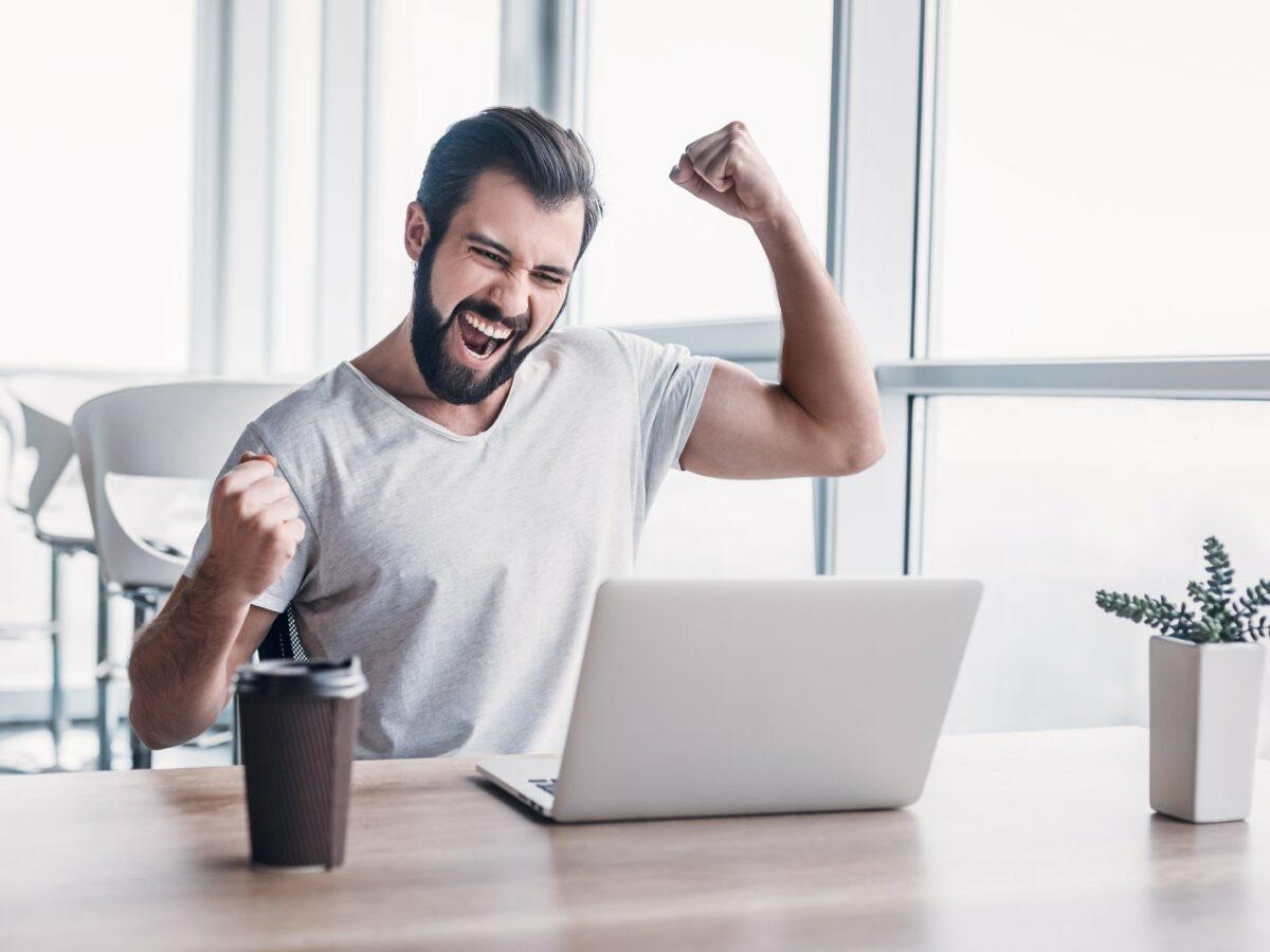 Mann sitzt vorm PC und freut sich