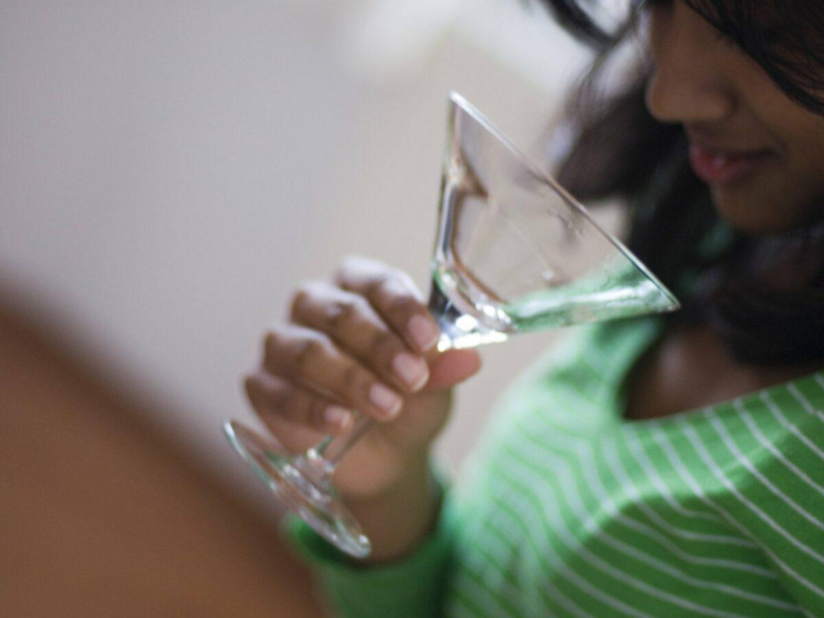 Frau schaut in ein leeres Cocktailglas.