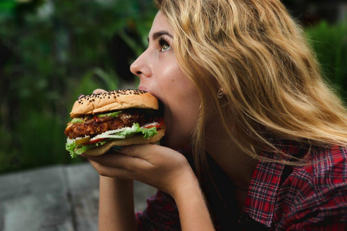 Frau beißt genüsslich in Burger.