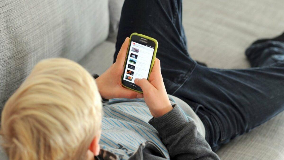 Junge mit Smartphone auf dem Sofa