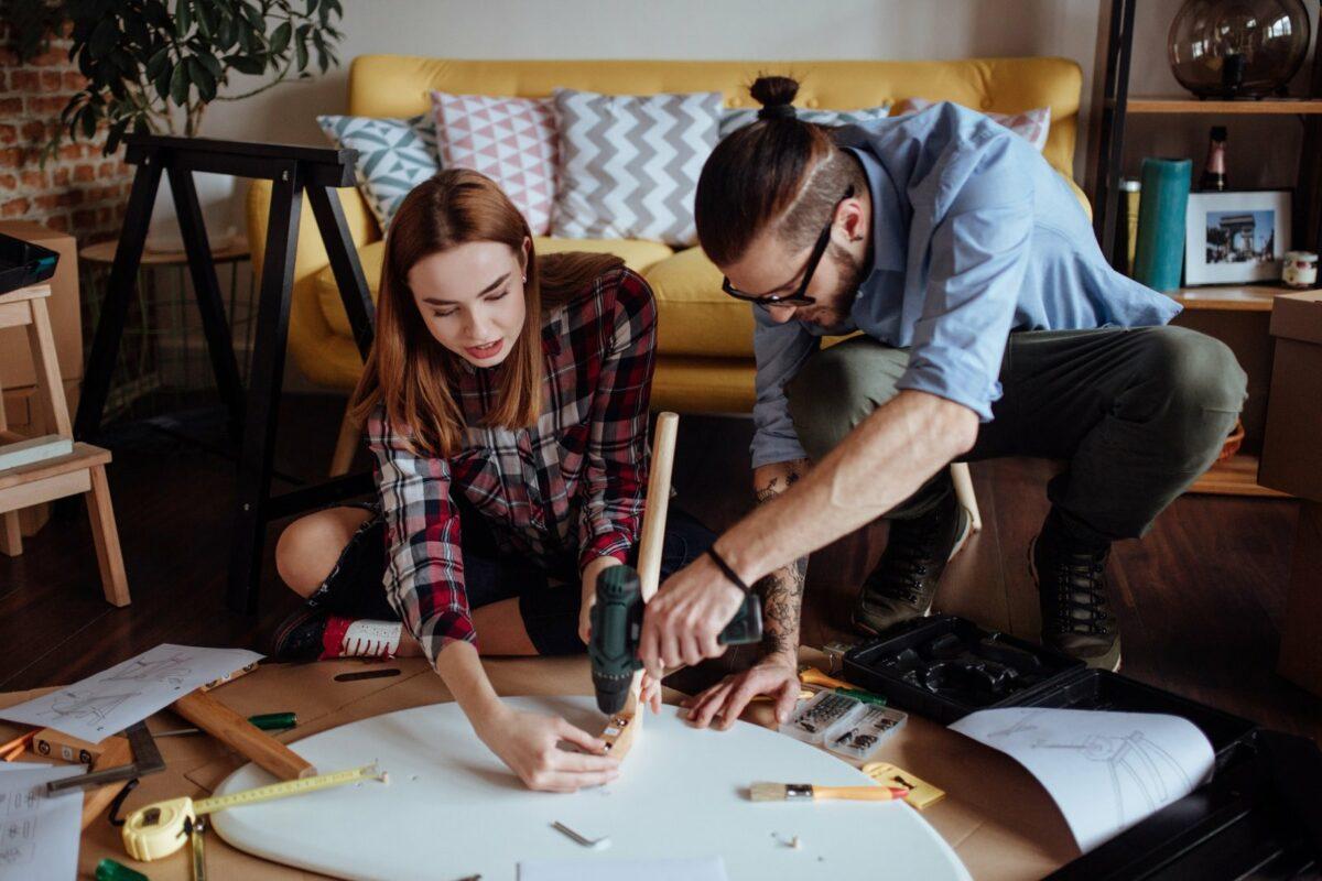 Frau und Mann bauen zusammen einen Tisch auf.