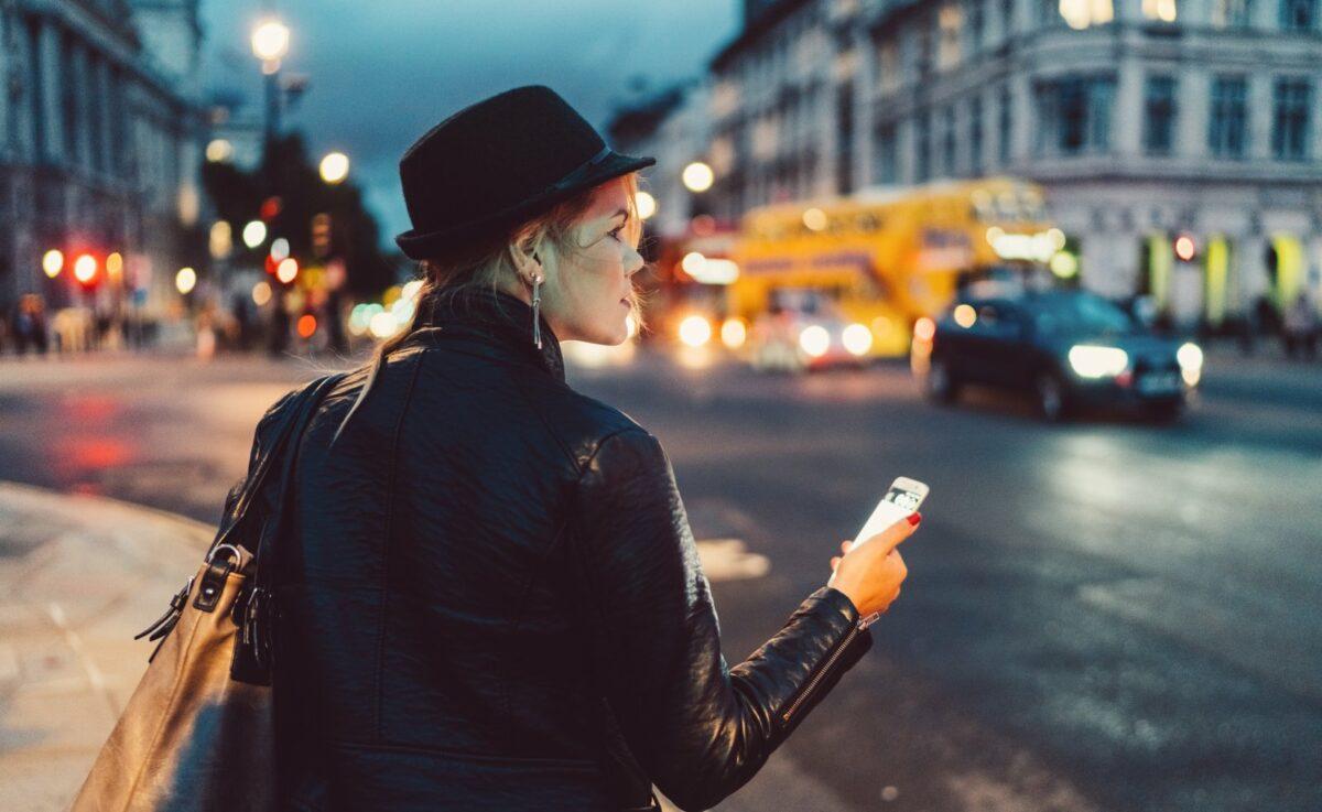 Frau mit Handy schaut sich in der Stadt um.