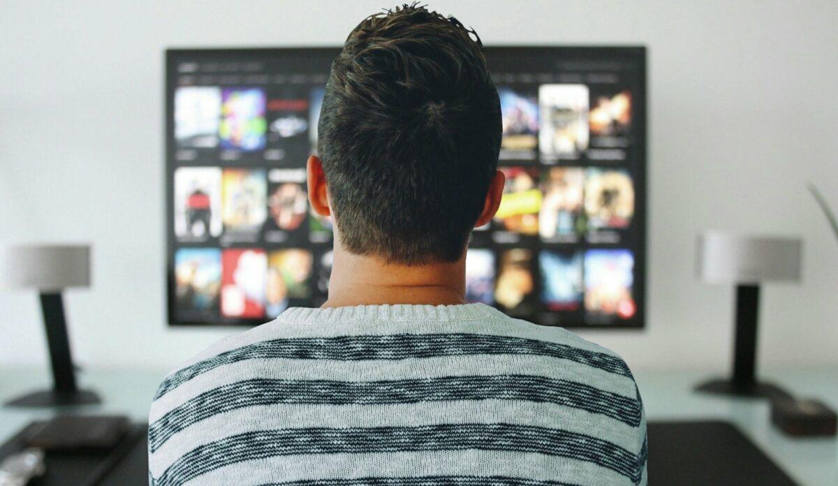 Ein Mann sitzt vor einem Fernseher