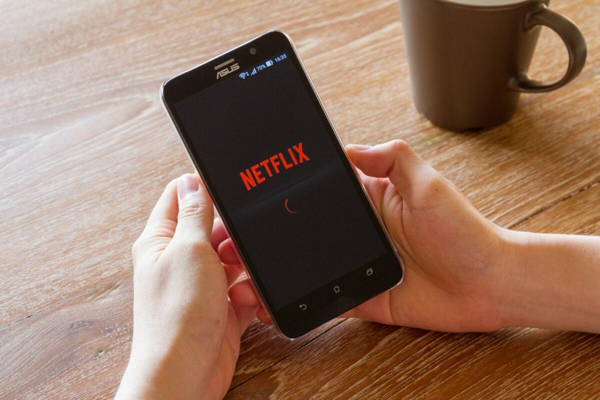 Mensch mit Handy und der Netflix-App