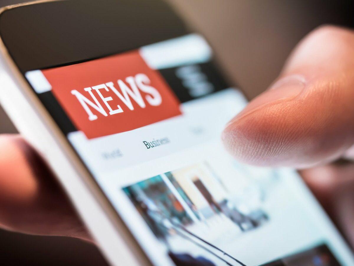 Smartphone mit geöffneter News-App in einer Hand