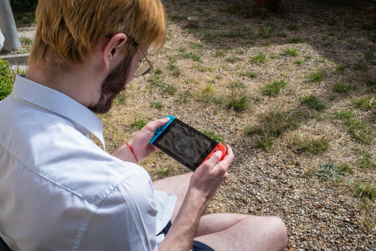 Mann spielt Nintendo Switch im Garten