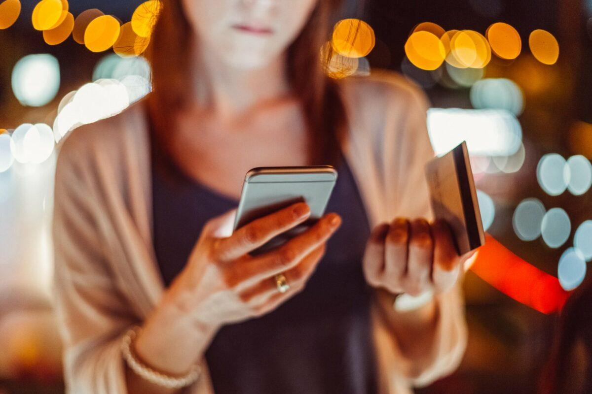 Eine Frau macht Online-Banking per Girocard und Handy.