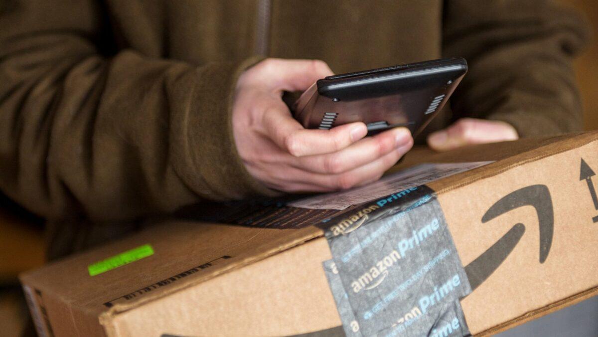 Jemand hält ein Amazon-Paket und sein Handy in der Hand.