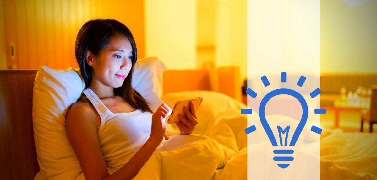 Handy im Bett und gedimmtes Licht