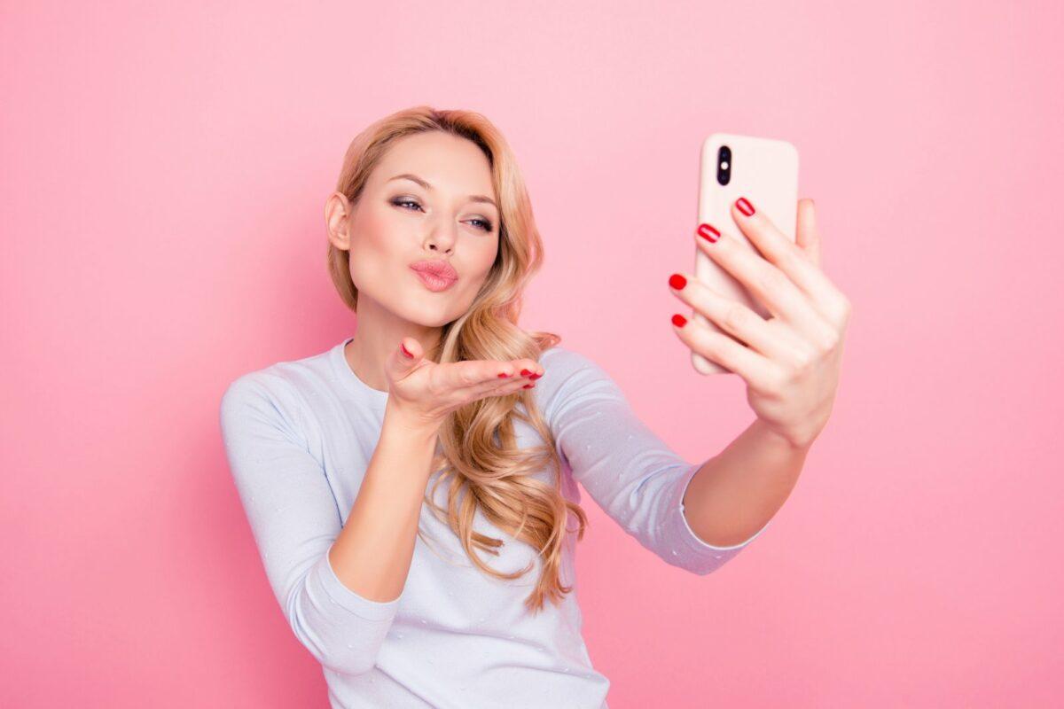 Frau macht Schmollmund und Handkuss für ein Selfie.