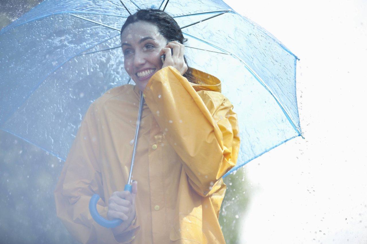 Frau mit Regenschirm und -jacke telefoniert mit ihrem Handy.