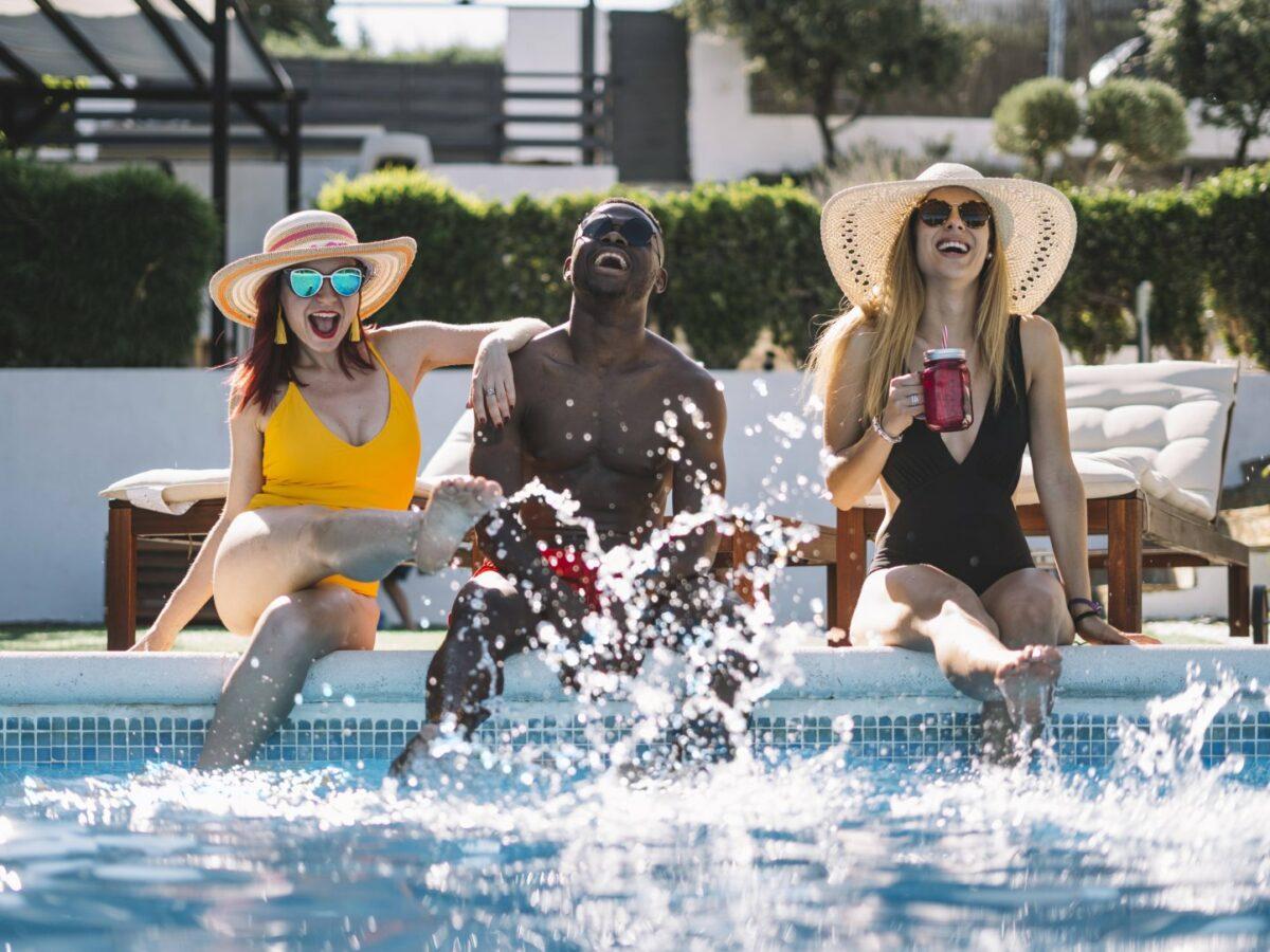 Drei Freunde sitzen am Pool und lachen