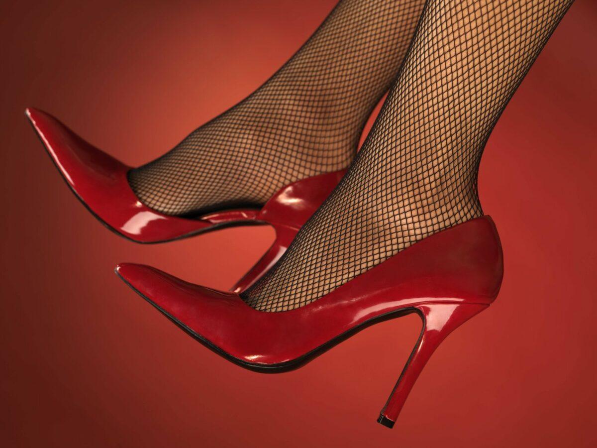 Rote High Heels und Netzstrümpfe vor rotem Hintergrund