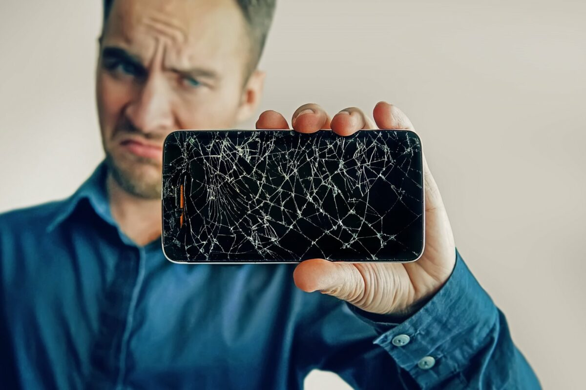 Mann mit kaputtem Handy in der Hand.