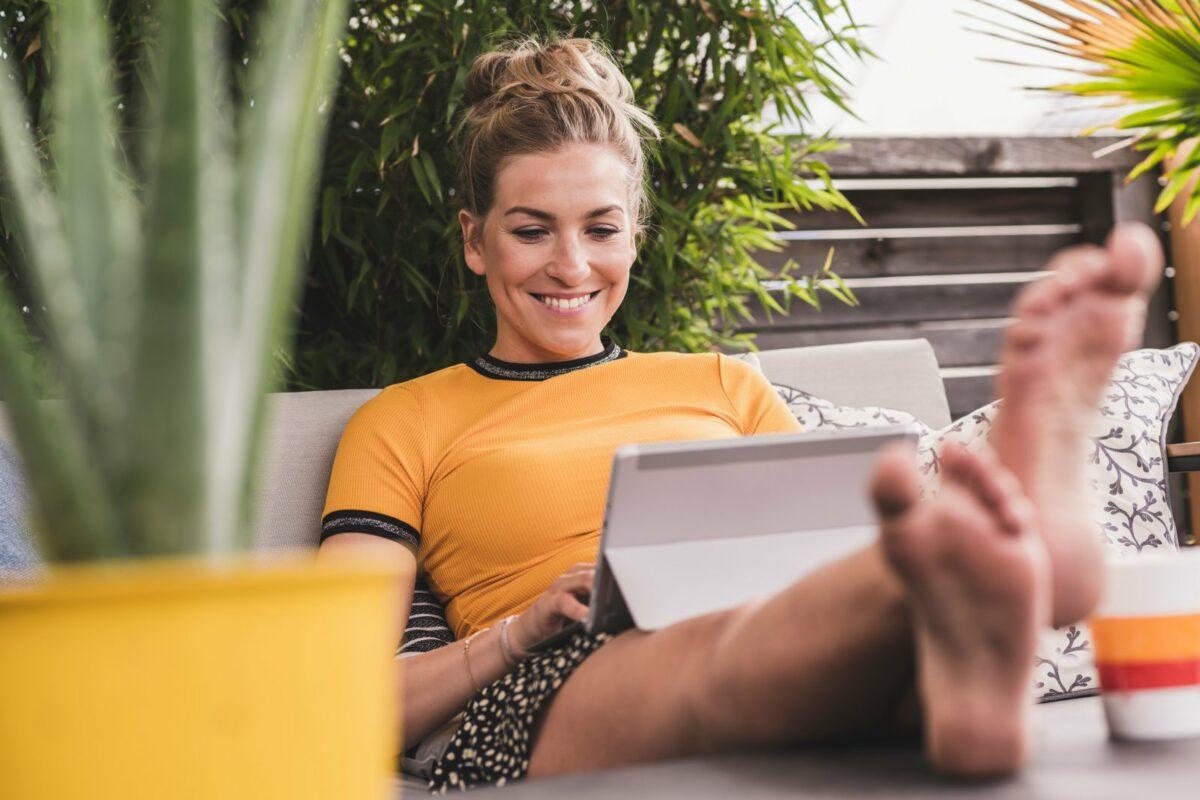 Frau sitzt lächelnd mit Tablet da.