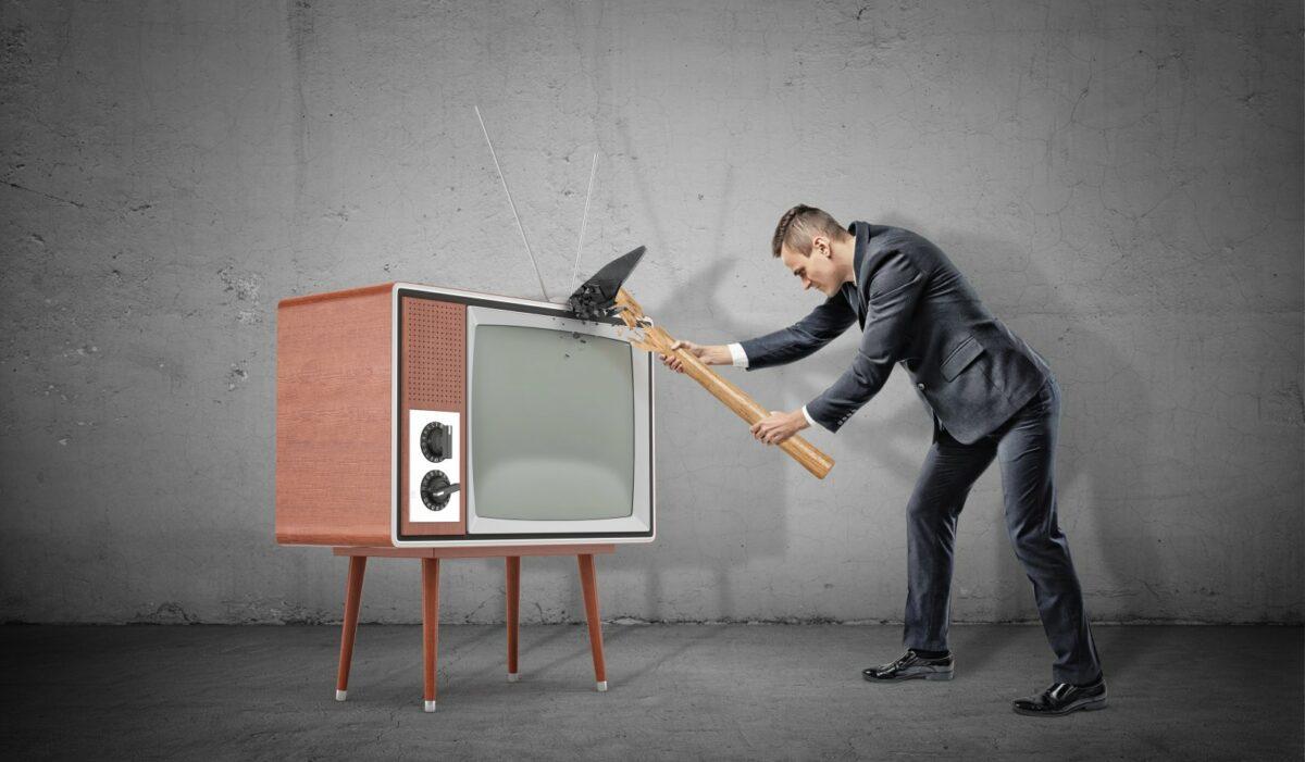 Mann haut mit Hammer auf einen Fernseher.