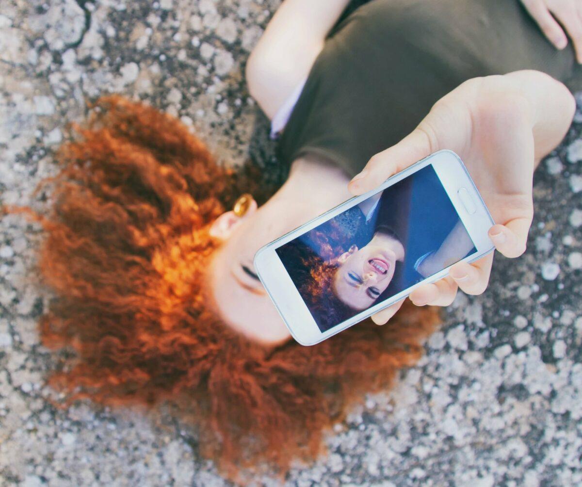 Rothaarige Frau hält ein Smartphone hoch