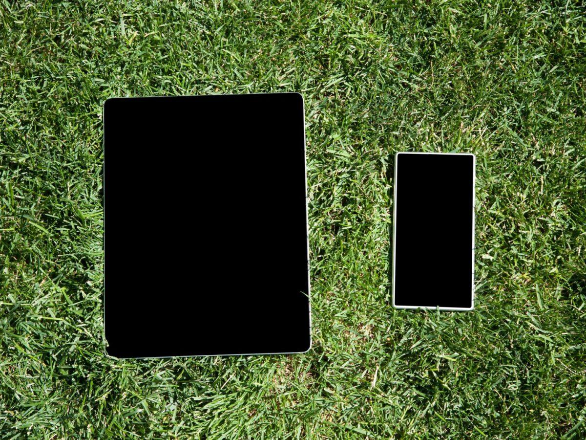 Smartphone und Tablet liegen auf Rasen