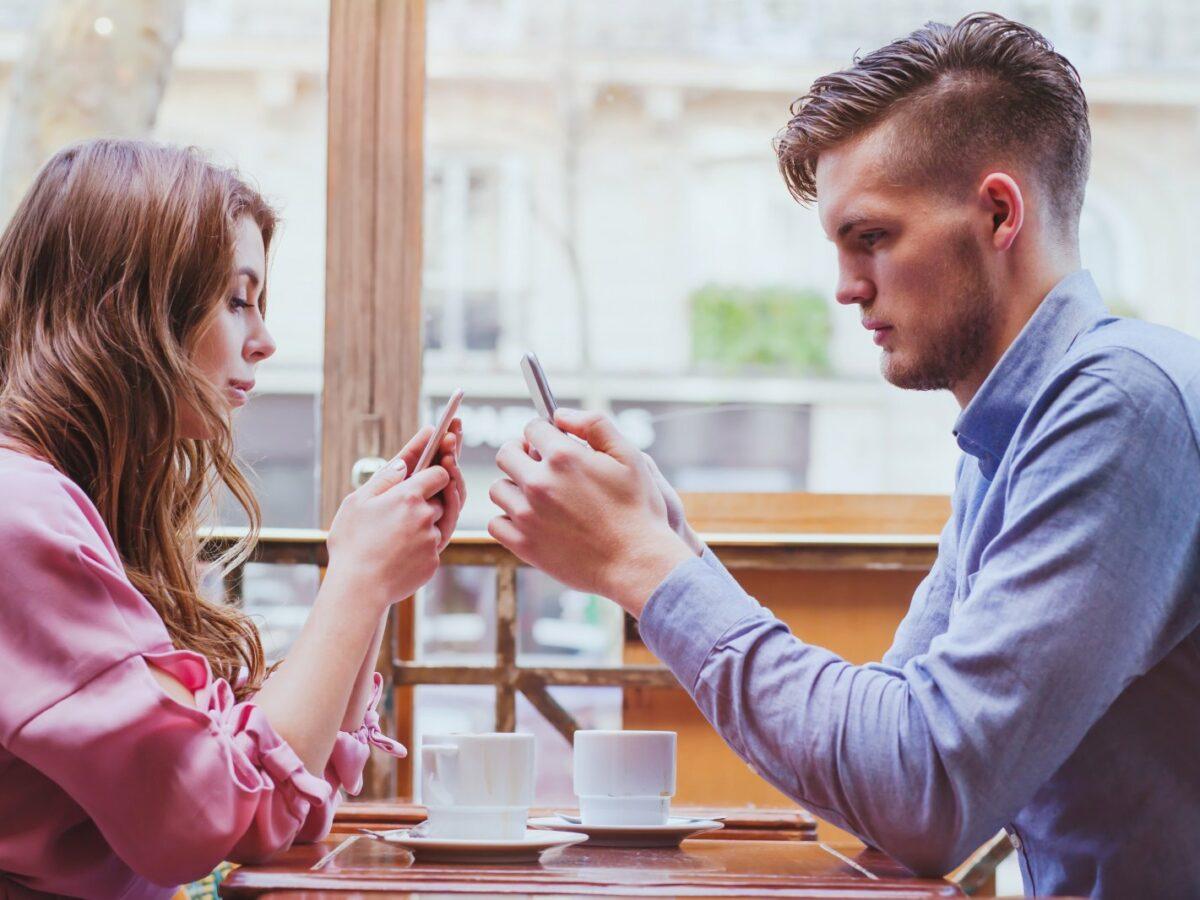 Mann und Frau starren auf ihre Handys.