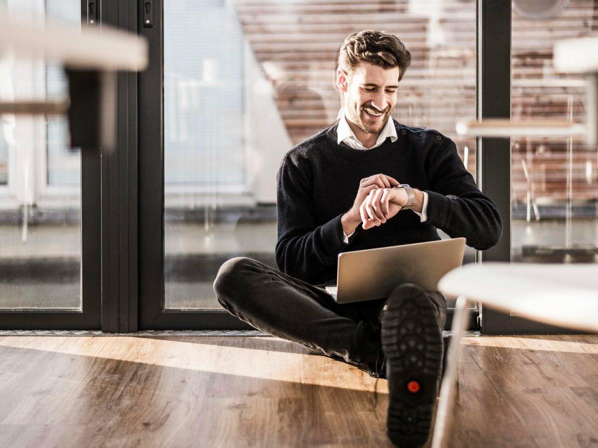 Mann mit Laptop und Smartwatch sitzend.
