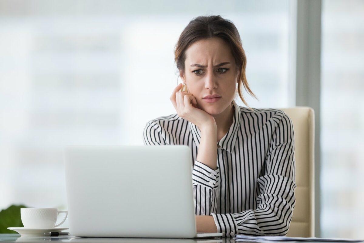 Frau sitzt skeptisch guckend vor einem Computer