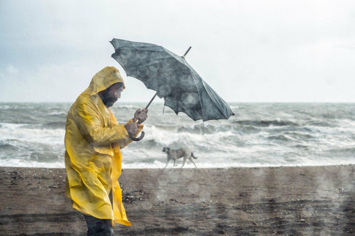 Mann in Regelmantel und Starkregen am Strand.