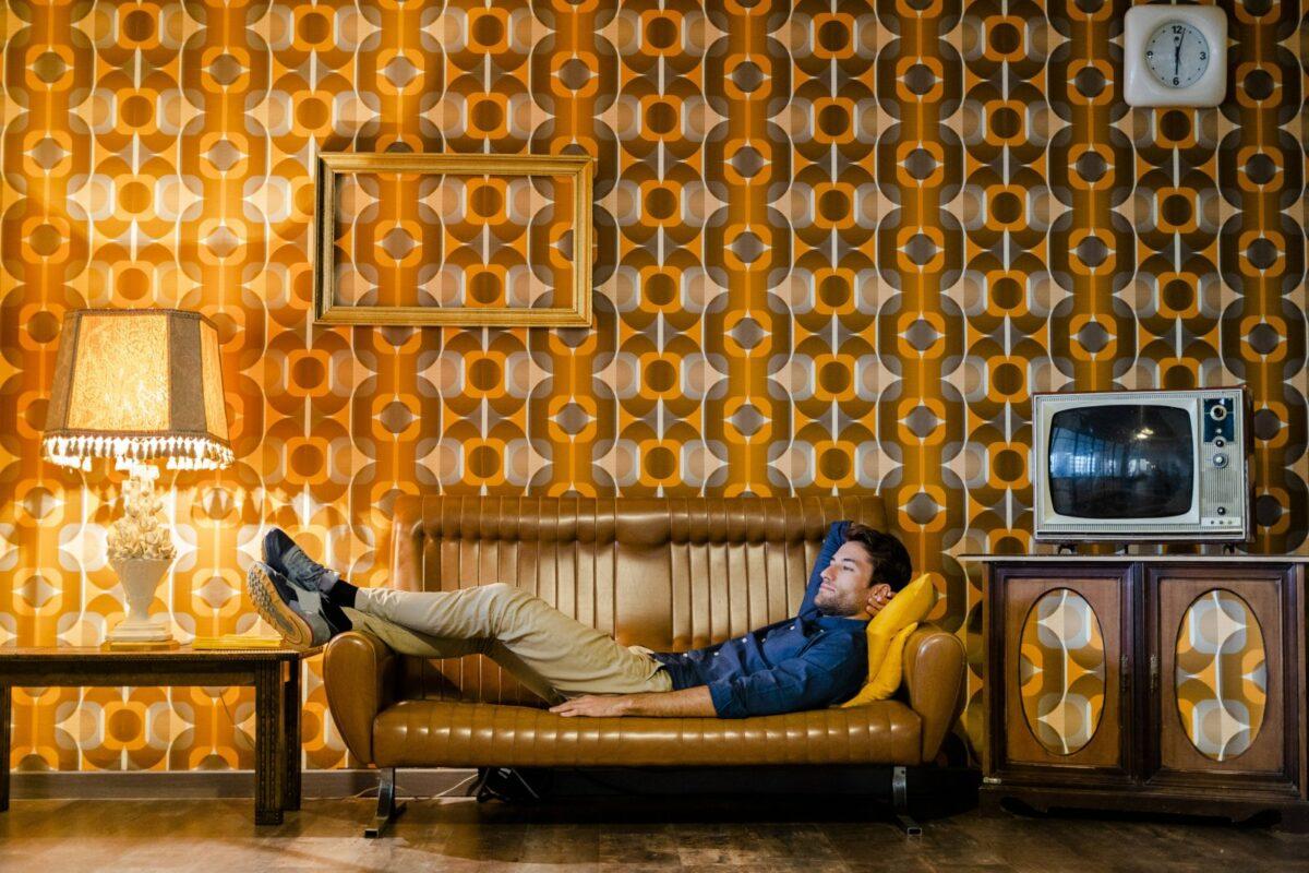 Mann liegt gemütlich auf der Couch.