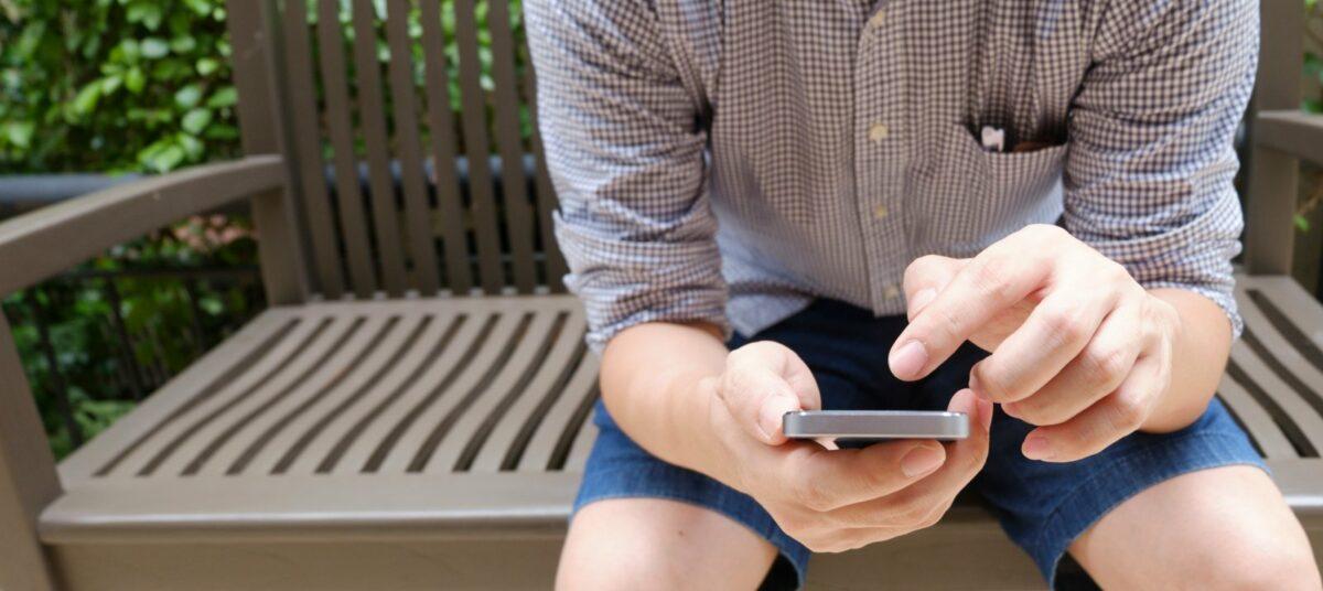 Ein Mann will auf einem Smartphone tippen.