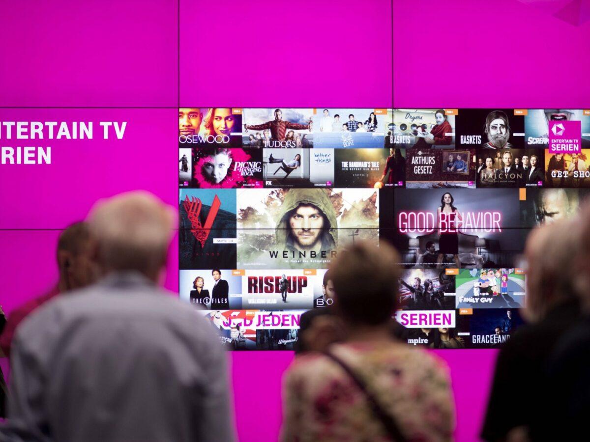 Menschen sehen auf magenta farbenen Bildschirm mit Serienvorschlägen.