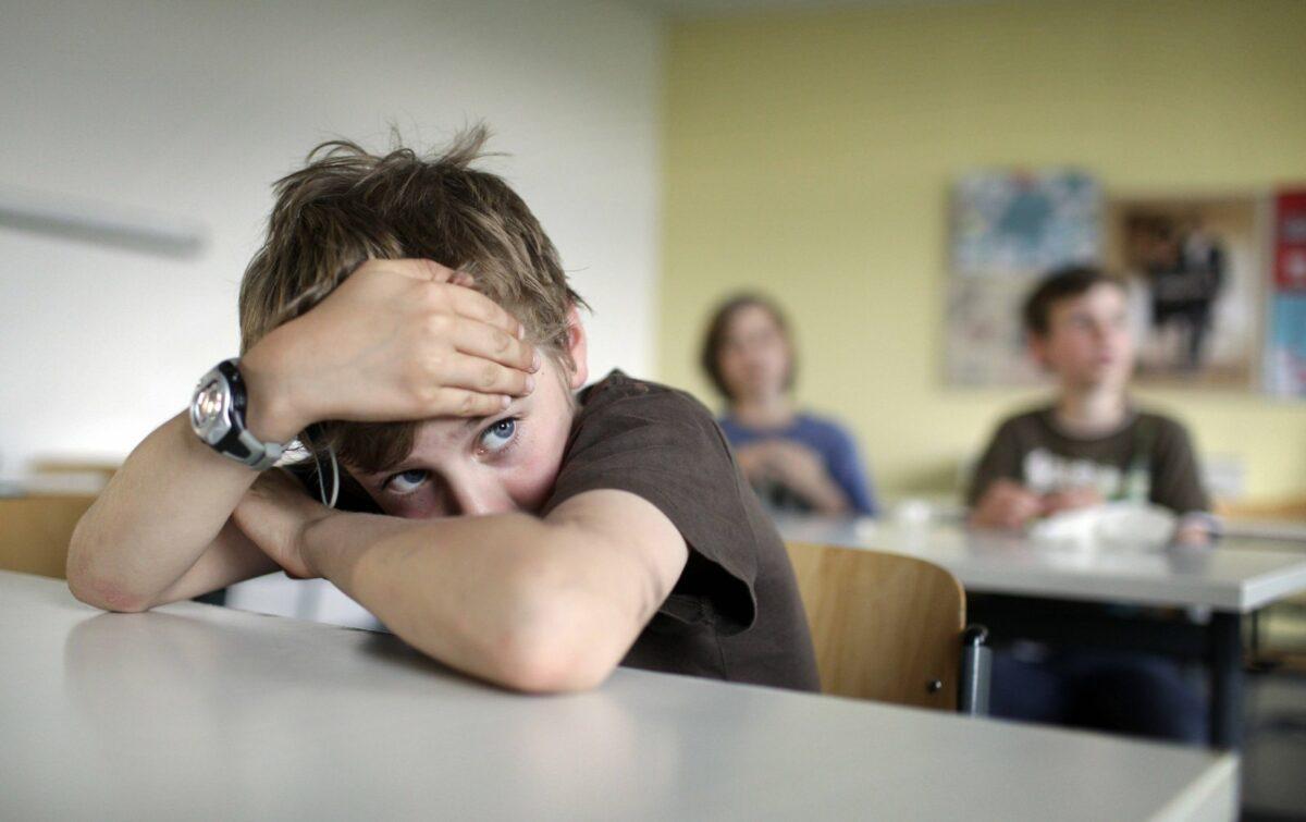 Das Bild zeigt einen traurigen Junge in der Schule