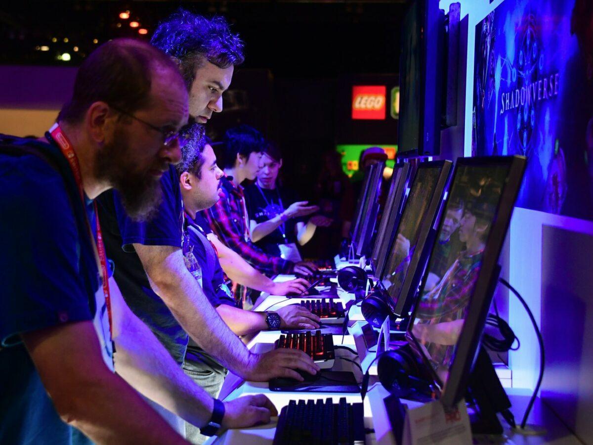Mehrere Männer stehen je an einem Rechner nebeneinander und spielen ein Videospiel