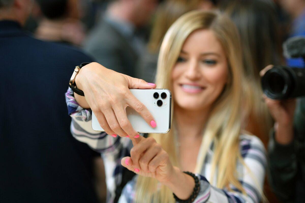 Frau macht ein Selfie mit dem iPhone 11.