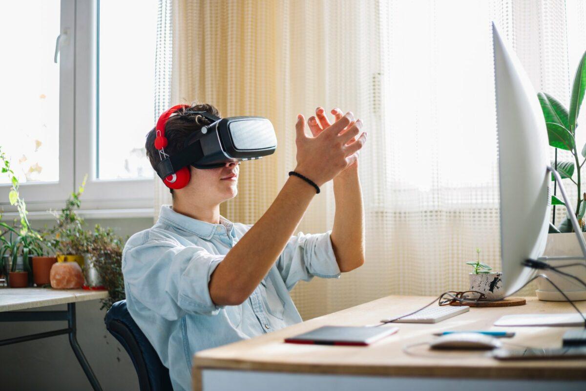 Mann sitzt mit VR Brille vorm PC