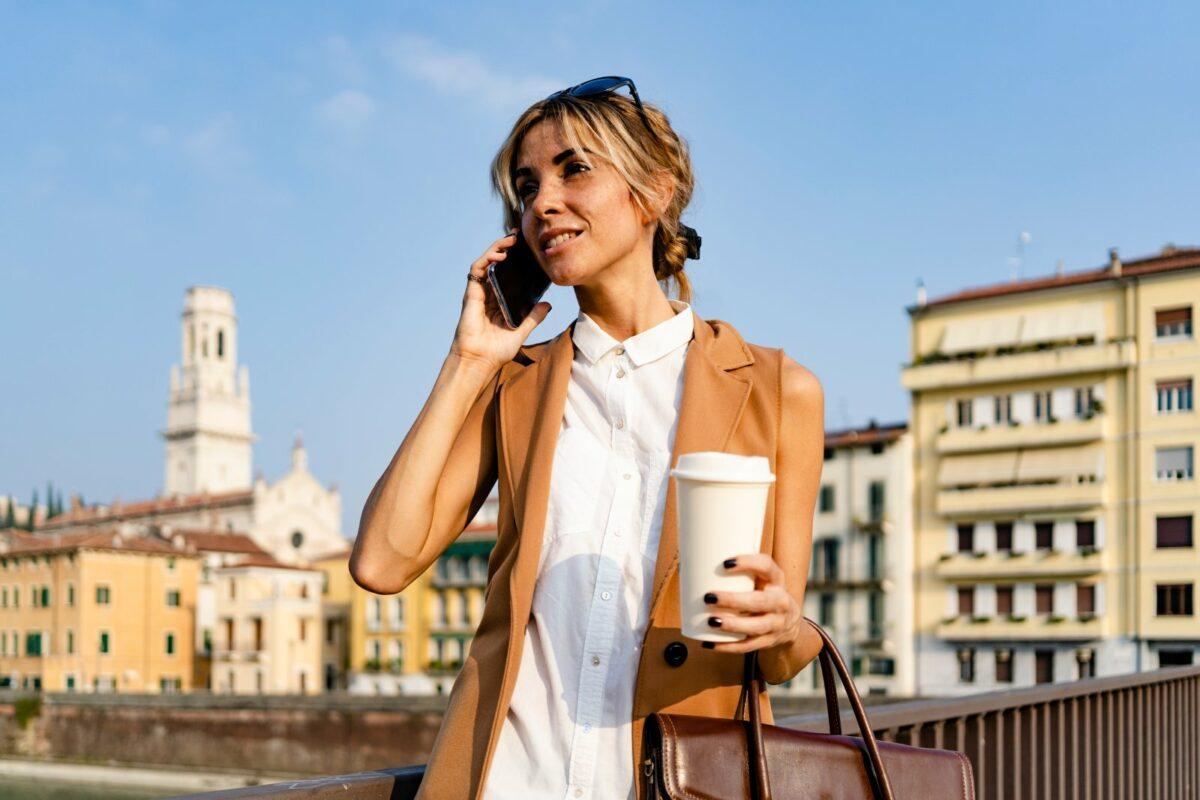 Frau telefoniert mit Kaffeebecher in der Hand.