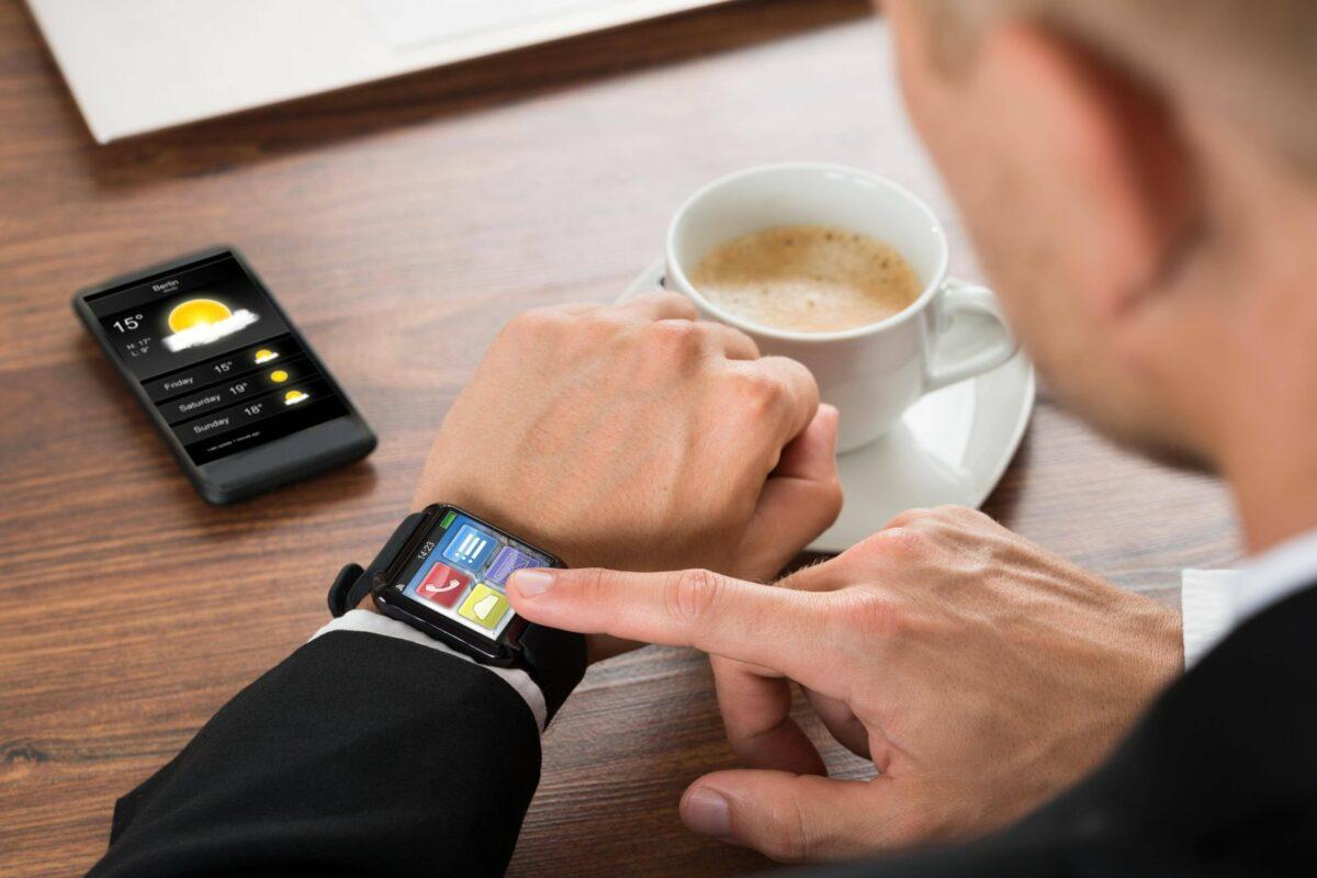 Hand und Smartwatch mit Wetteranzeige.