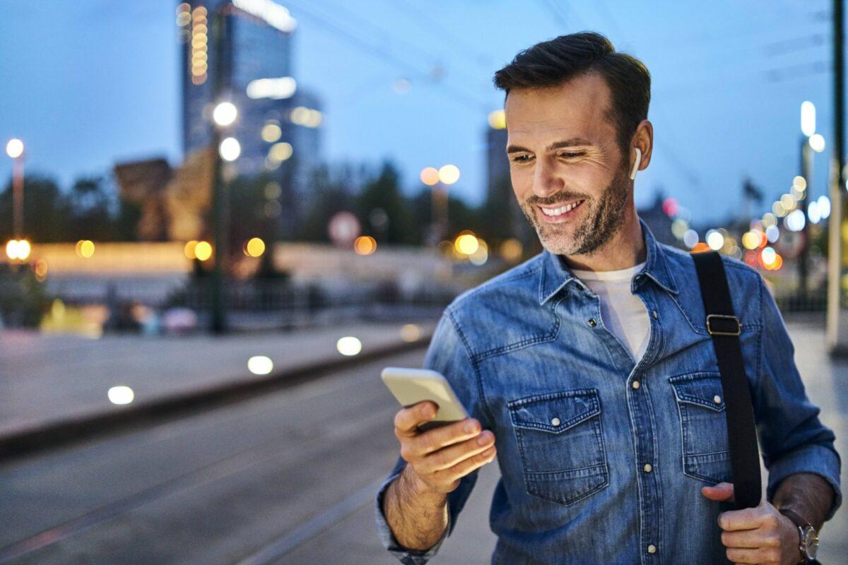 Mann guckt glücklich auf sein Handy