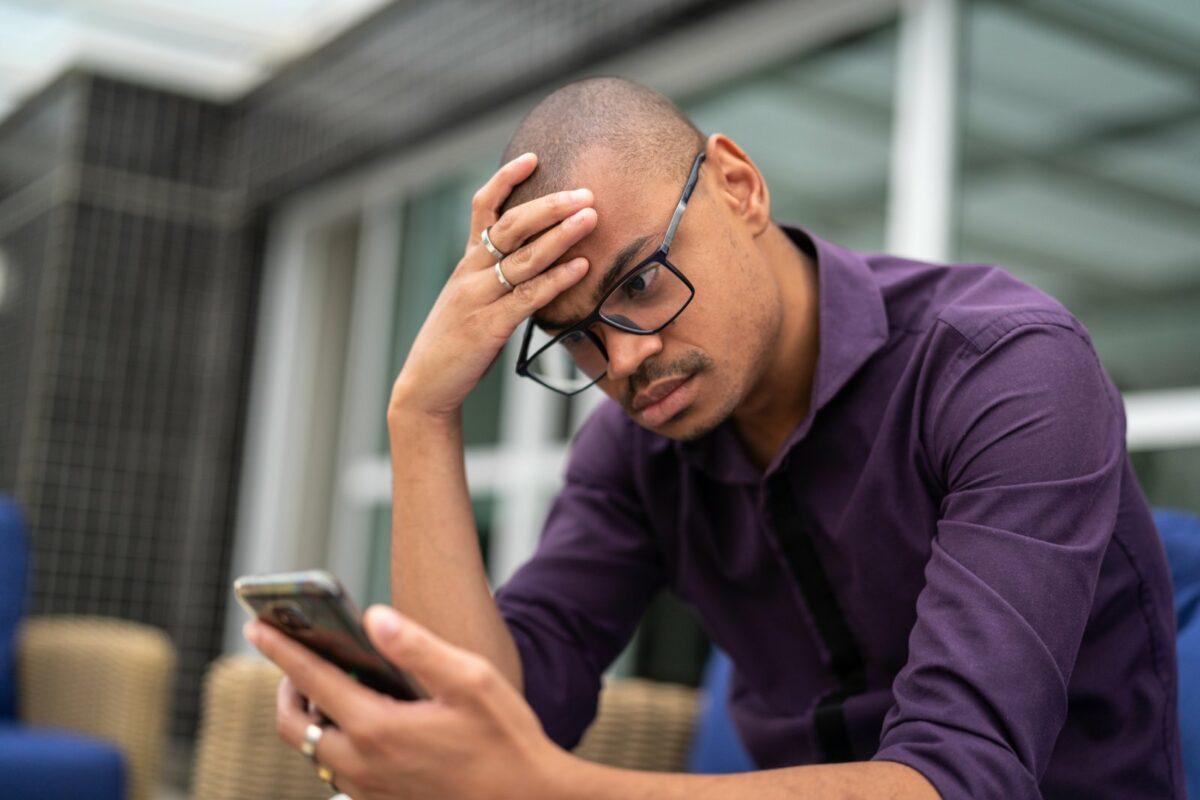 Mann schaut genervt auf sein Handy.