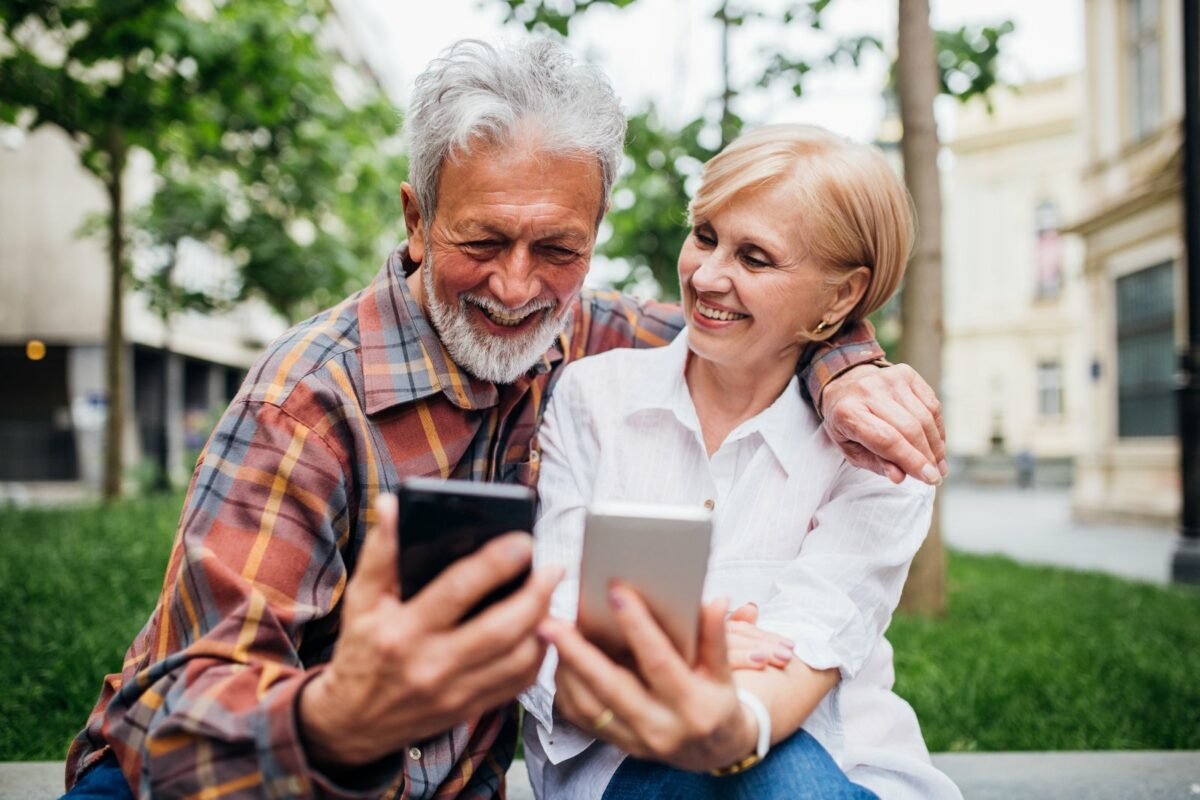 Ein älteres Paar schaut glücklich auf ihre Smartphones.